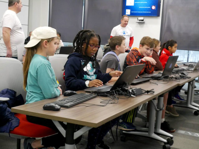Associates from World Wide Technology work with St. Louis-area students at the Hour of Code event, part of the company's STEM initiatives.