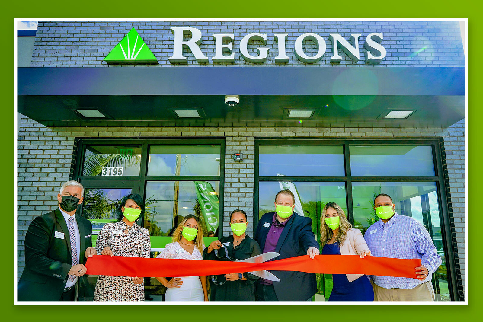 Associates cutting the ribbon in front of new regions branch