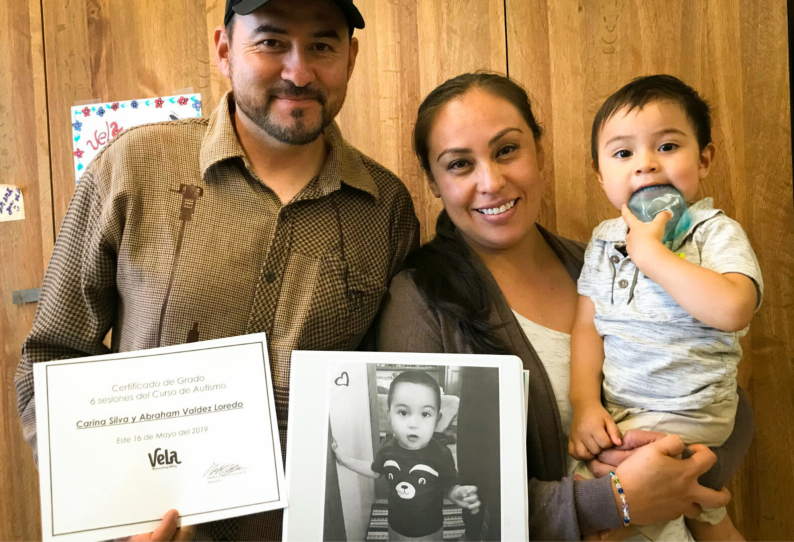 Photo of mother, father and child, holding up a VELA certificate